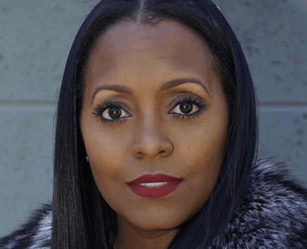 Keshia Knight Pulliam in front of a wall.
