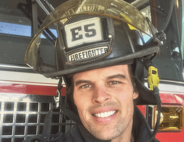 Kevin Wendt in a firefighter helmet in front of a red truck.