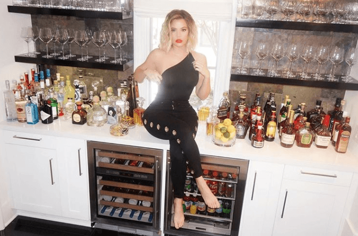 Khloe Kardashian sitting on a counter in her home