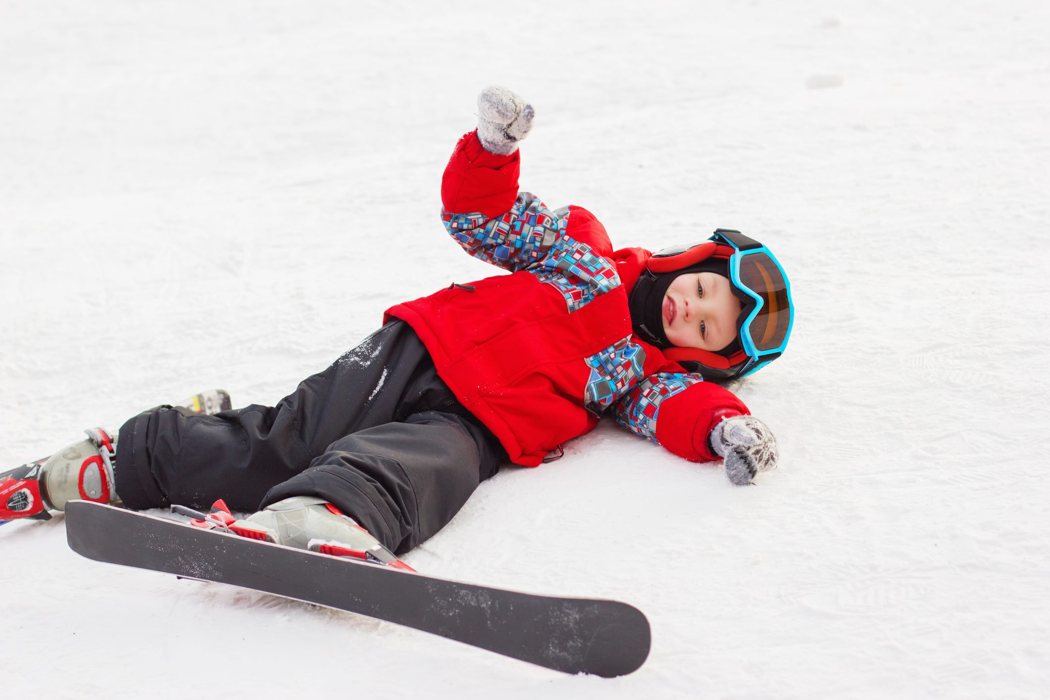 Little cute boy with skis and a ski outfit.