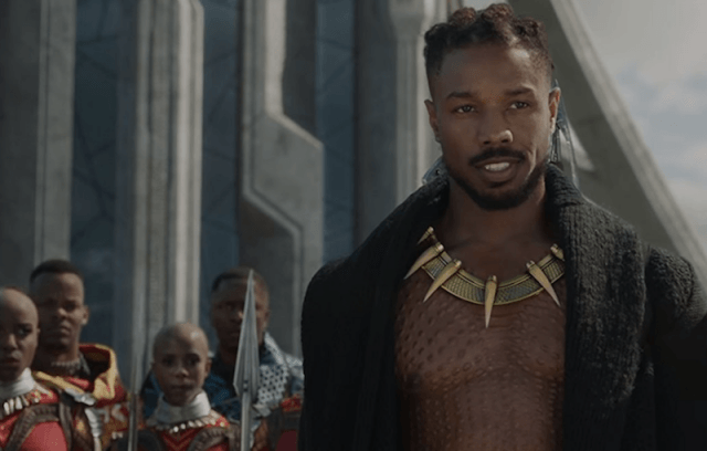 Killmonger standing while wearing a gold necklace and black cloth.