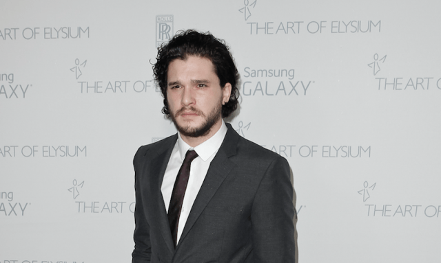 Jon Snow posing in a gray suit at Art of Elysium.