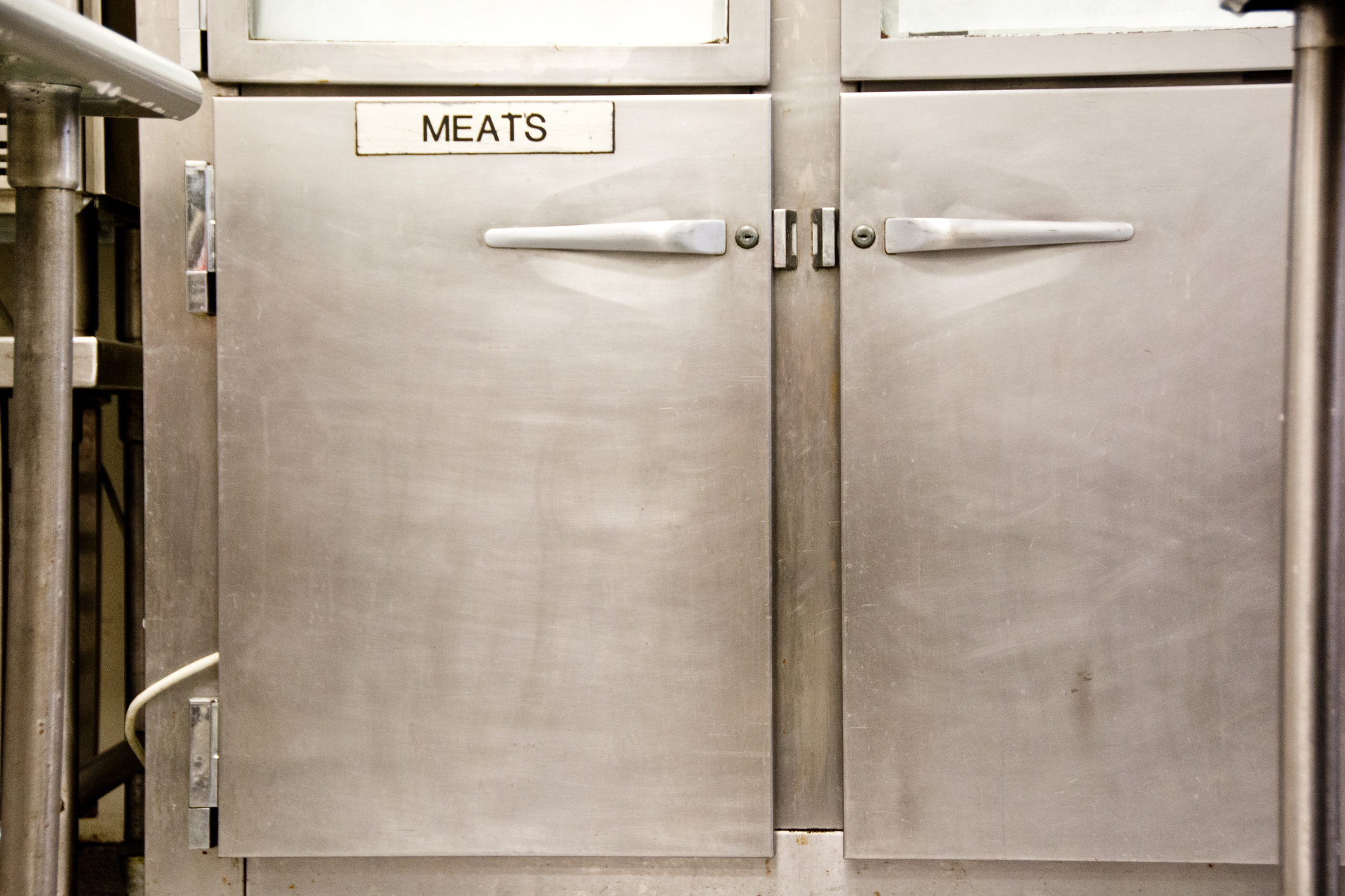 This cooler in a commerial kitchen is specially labeled for meat only.
