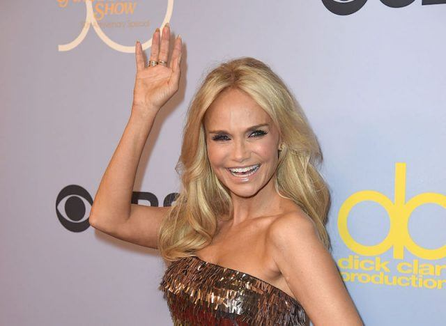 Kristin Chenoweth smiling and waving while wearing a gold dress.