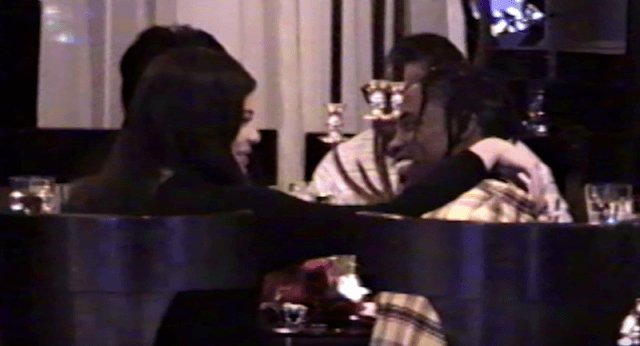 Travis Scott sitting at a dinner table with Kylie Jenner.