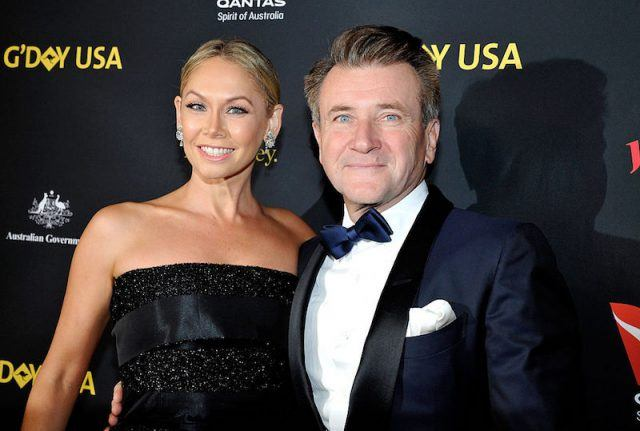Kym Johnson and Robert Herjavec on a red carpet.