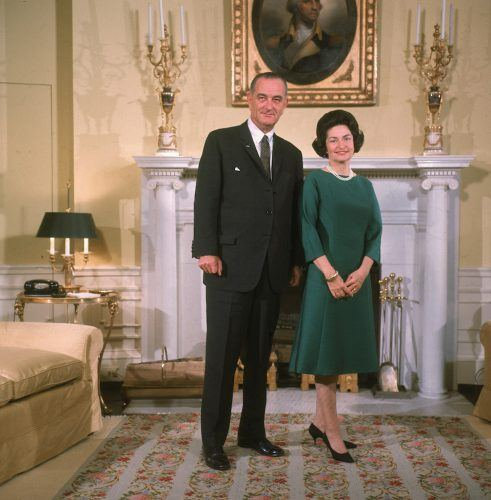 American president Lyndon Baines Johnson poses with his wife Lady Bird Johnson in front of a fireplace at the White House