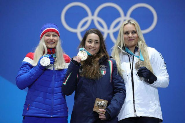 Three Olympic athletes posing with their medals.