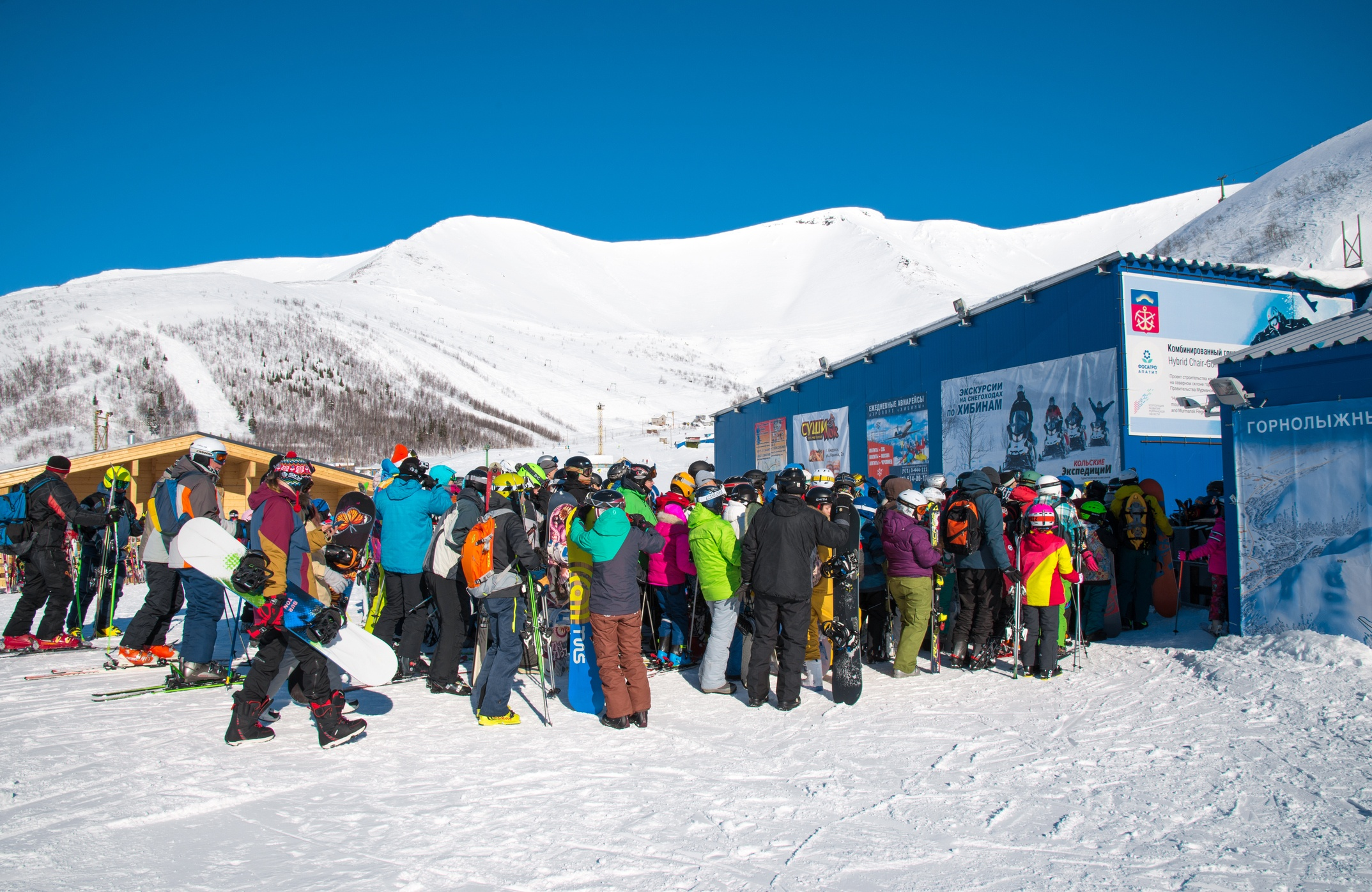 Skiers queue to the lift in ski resort, a lot of people. North Russia, Khibiny Mountains