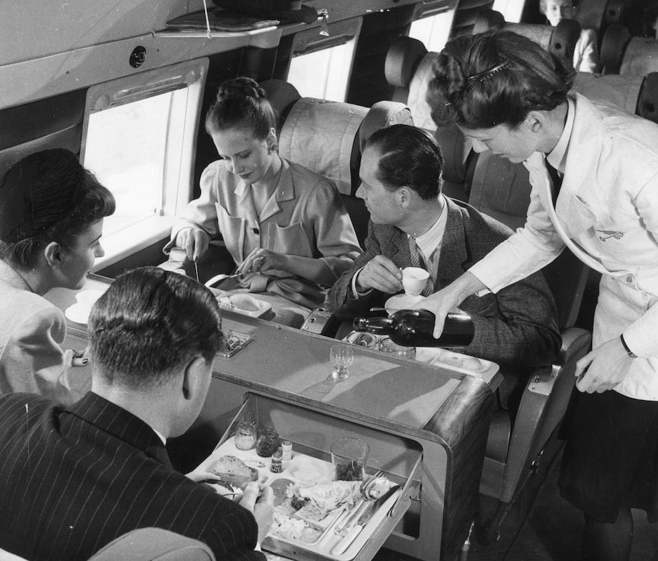A stewardess serving drinks whilst passengers have lunch aboard a BEA Vickers Viking passenger plane