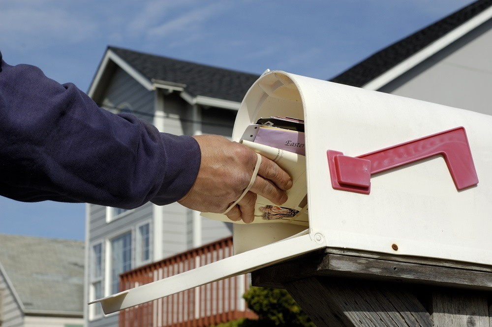 Mailman's arm inserting a bundle of mail
