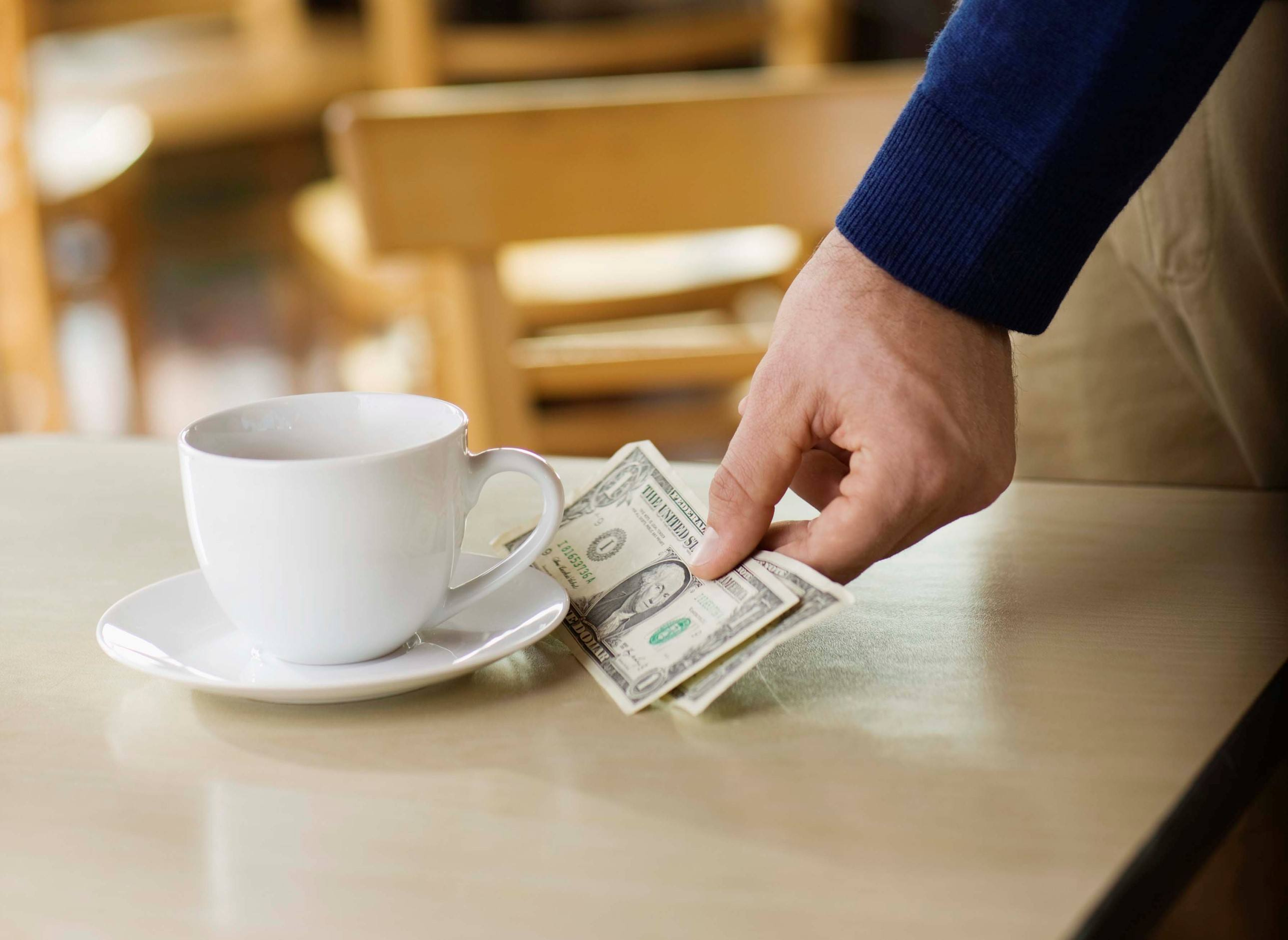Man leaving tip on table at cafe