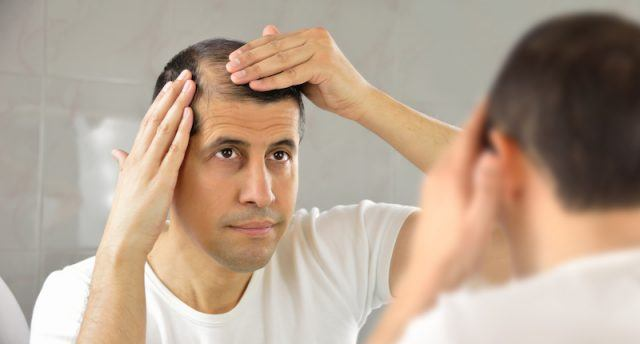 A balding man inspects his hair in the mirror.