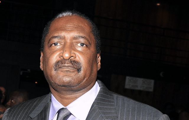 Mathew Knowles poses in a gray suit and purple shirt.