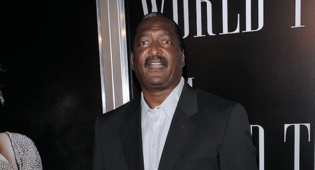 Mathew Knowles speaking at an event while wearing a black suit.
