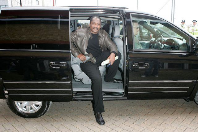 Mathew Knowles posing inside a black car.