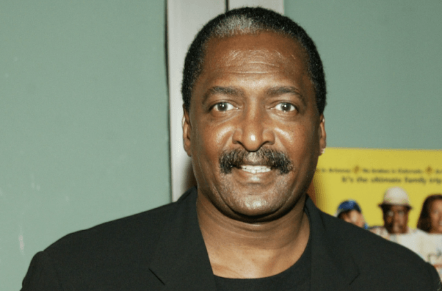 Mathew Knowles smiling while posing at an event.