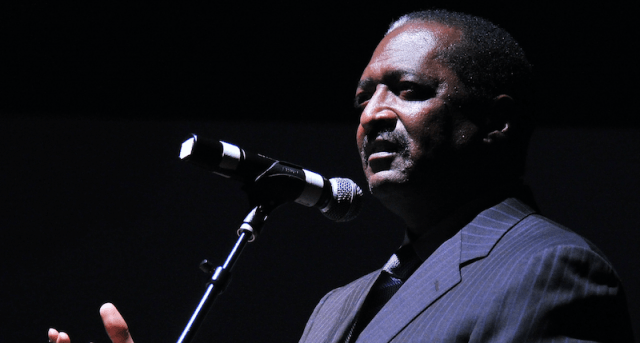 Mathew Knowles in front of a microphone.