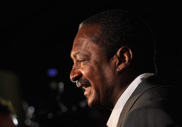 Mathew Knowles standing in a gray suit.