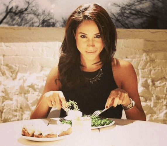 Meghan Markle eating at a table.