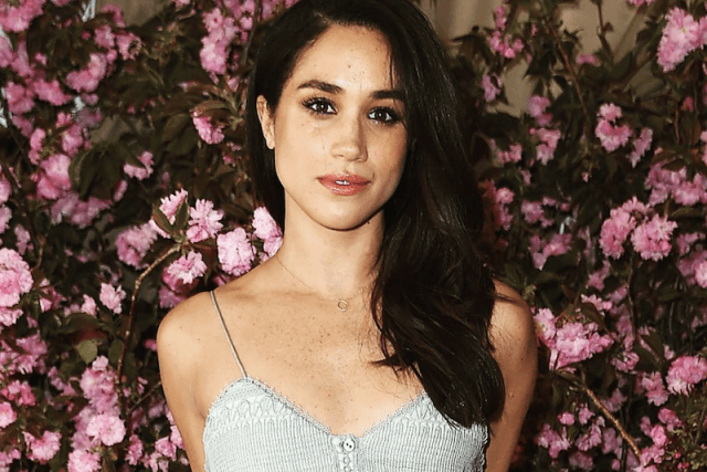 Meghan Markle posing in front of a wall of pink flowers.