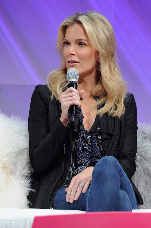 Megyn Kelly sitting on a couch with a microphone on her hand.