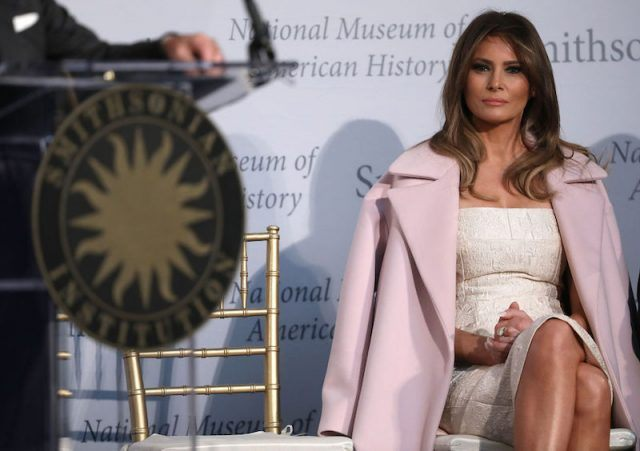 Melania Trump sitting in a white dress and a light pink coat.