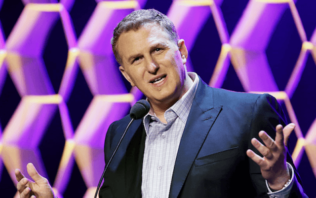 Michael Rapaport holding up his hands while speaking in front of a microphone.