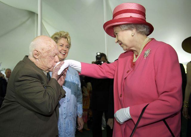 Mickey Rooney kissing Queen Elizabeth's hand.