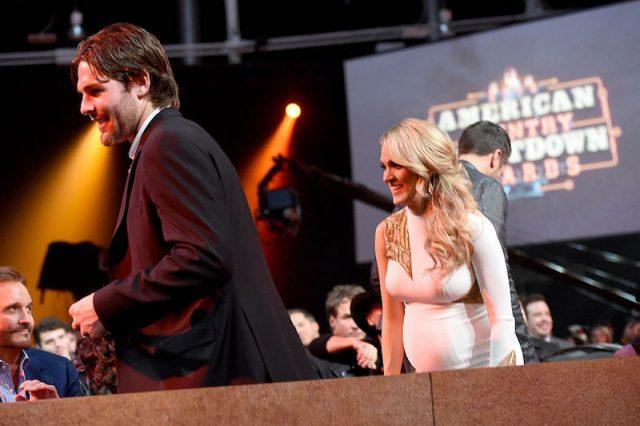 A pregnant Carrie Underwood walking behind Mike Fisher at an award show.