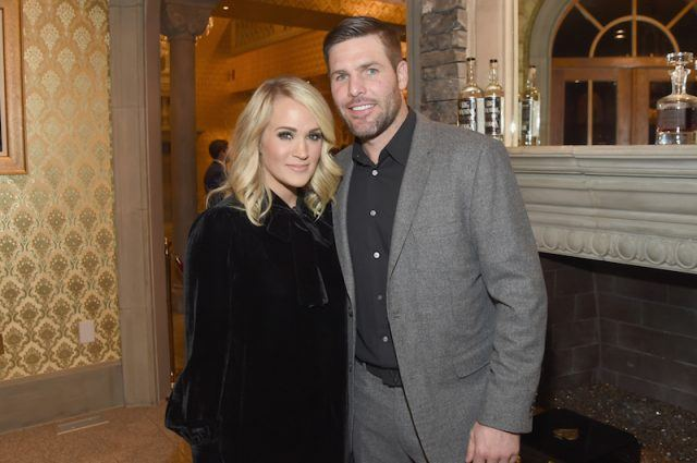 Mike Fisher and Carrie Underwood posing in front of a fireplace.
