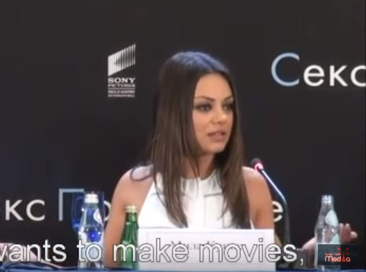 Mila Kunis reacts to a reporter.