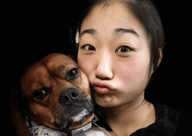 Mirai making a goofy face in a selfie with her dog.