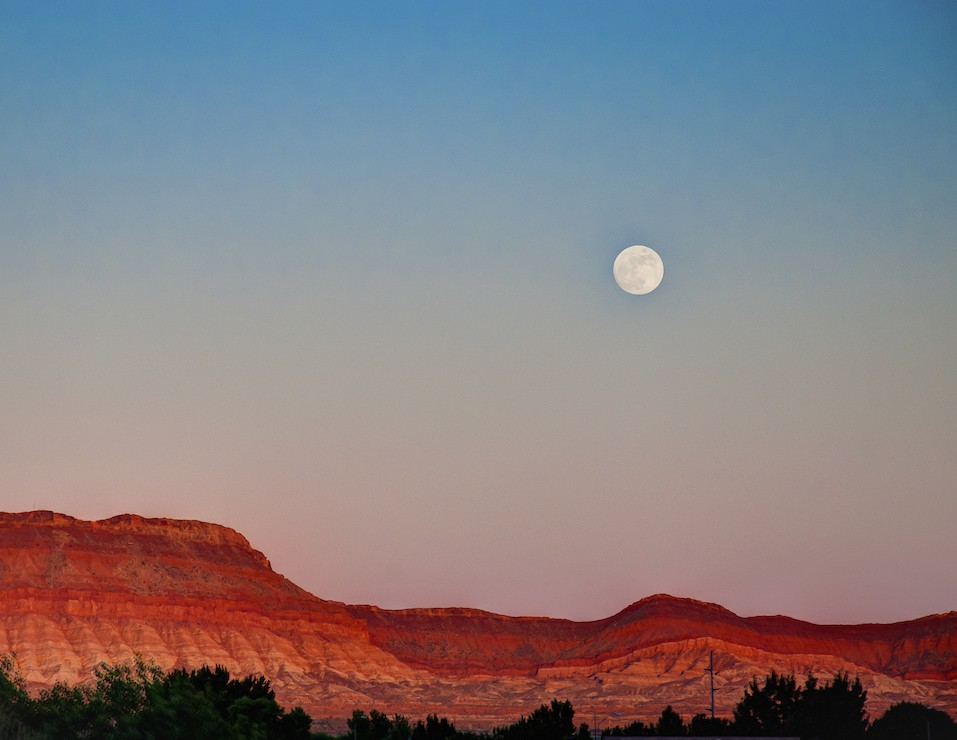 Full moon rising over the mountains of St. George Utah.
