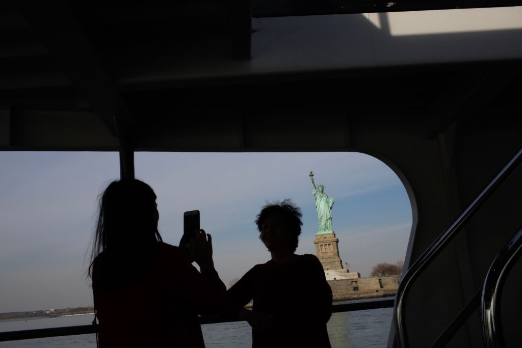 Tourists taking a photo of the statue of liberty