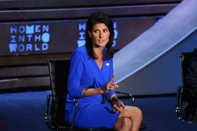 Nikki Haley sitting in a blue dress on a stage panel.