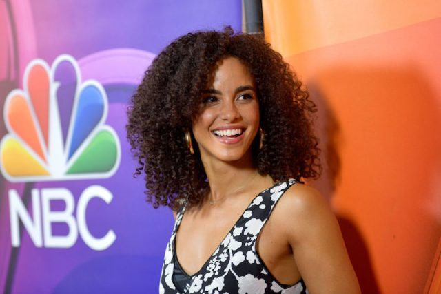 Parisa Fitz-Henley posing in a black and white floral dress and smiling.