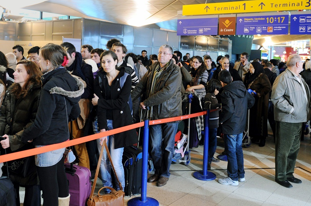 Passengers queue after flights have been cancelled as security officers