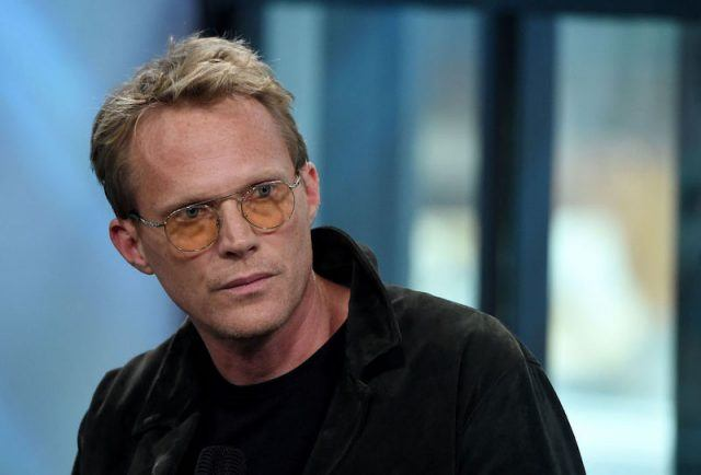 Paul Bettany wearing yellow glasses and a black shirt.