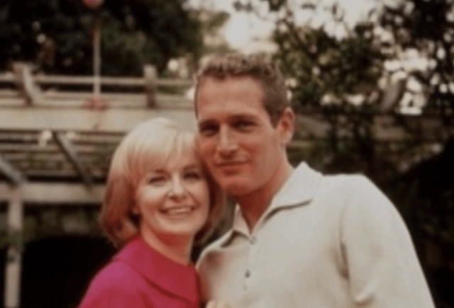 Paul NewmanandJoanne Woodward smiling while standing outdoors.