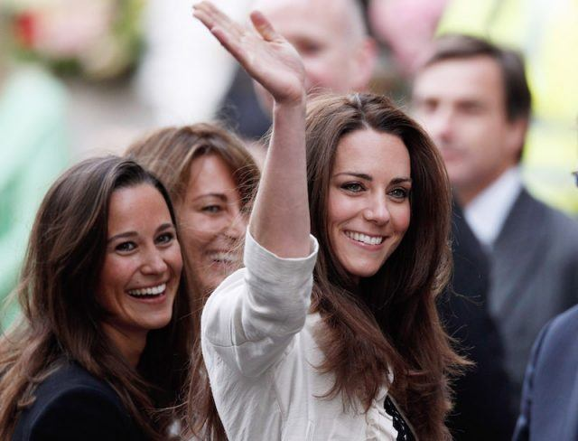 Pippa Middleton smiles as Kate Middleton waves.