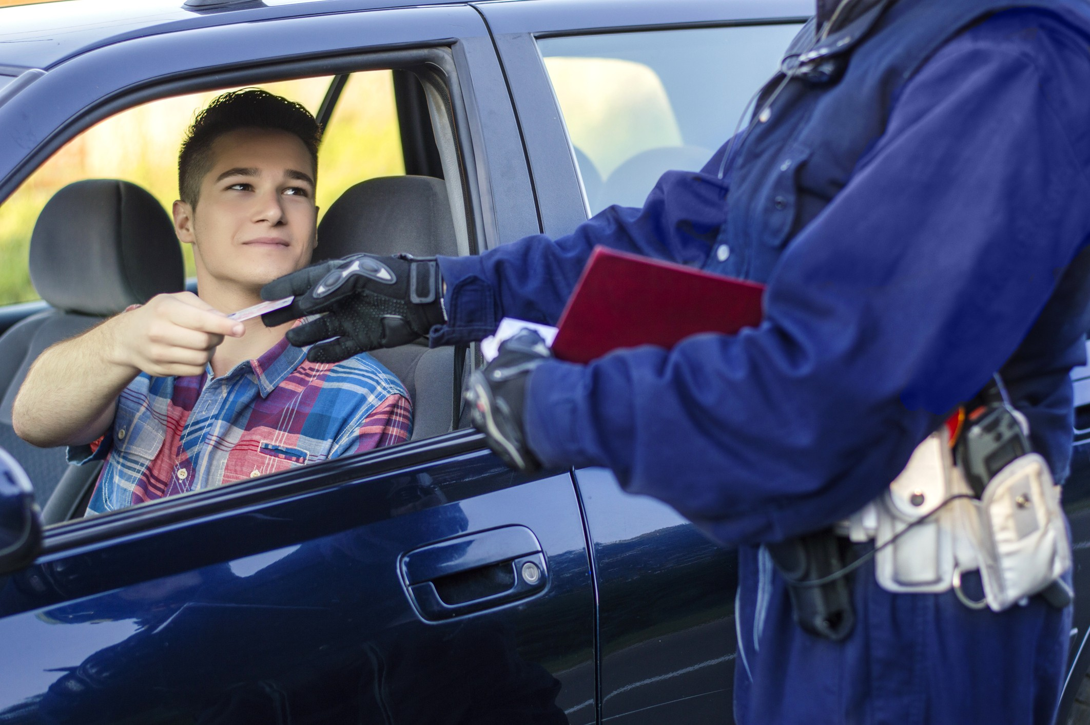 Young man handing over identification during a police stop