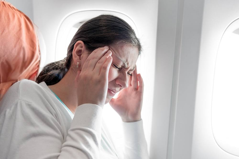 Portrait of a woman with a headache on an airplane