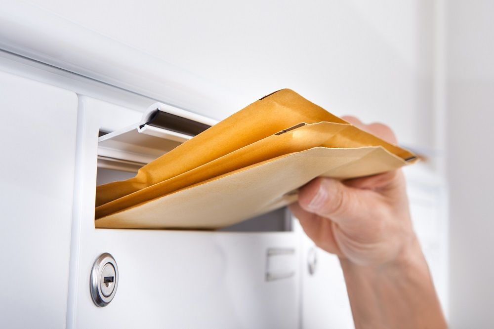 Postman Putting Letters In Mailbox
