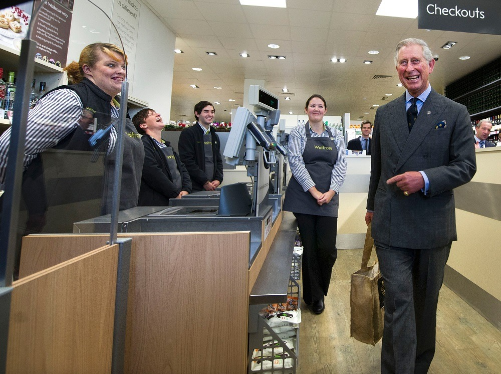 Prince Charles, Prince Of Wales (R) leaves the check-out with the bag of produce