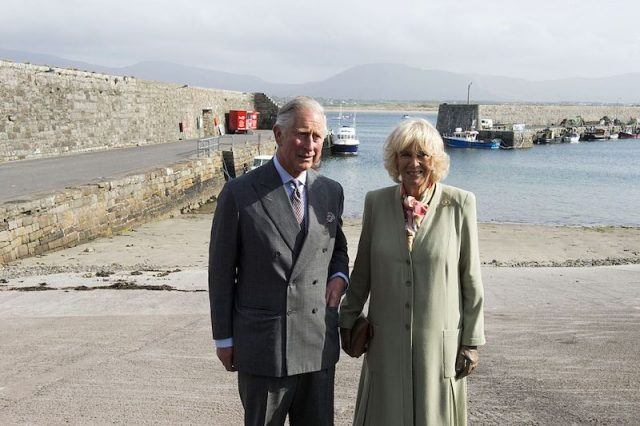 Prince Charles and Camilla Parker Bowles standing near a port.