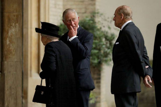 Prince Philip, Prince Charles and Queen Elizabeth walking together.