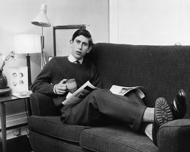 Prince Charles sitting on a couch reading a newspaper.
