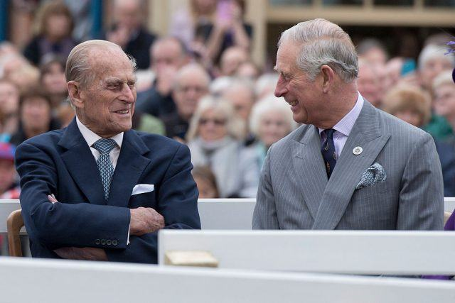 Prince Charles and Prince Philip smiling and speaking to each other.