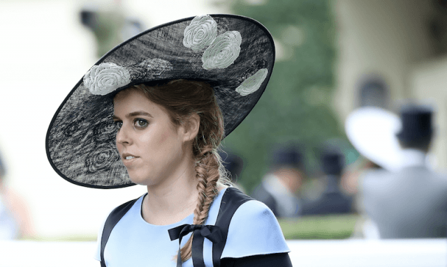 Princess Beatrice in a blue dress and large black hat.